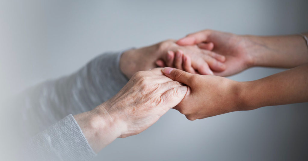elderly woman holding hands